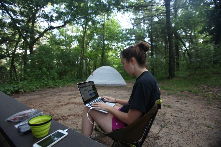 Milwaukee Journal Sentinel reporter Chelsey Lewis works at a campsite at Mirror Lake State Park outside Baraboo.
