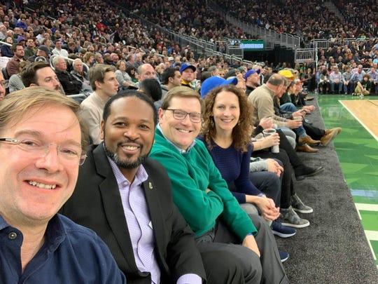 Milwaukee County Executive Chris Abele (foregrounds) sits next to Milwaukee Common Council President Ashanti Hamilton at a Milwaukee Bucks game.