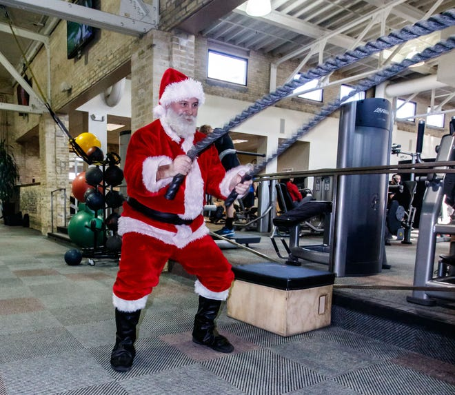 Derek Byrne works the battle ropes in full Santa attire at the Wisconsin Athletic Club in Wauwatosa on Monday, Dec. 10. Derek, who does strong man competitions and is involved in charity work, dresses up to encourage others to work out.