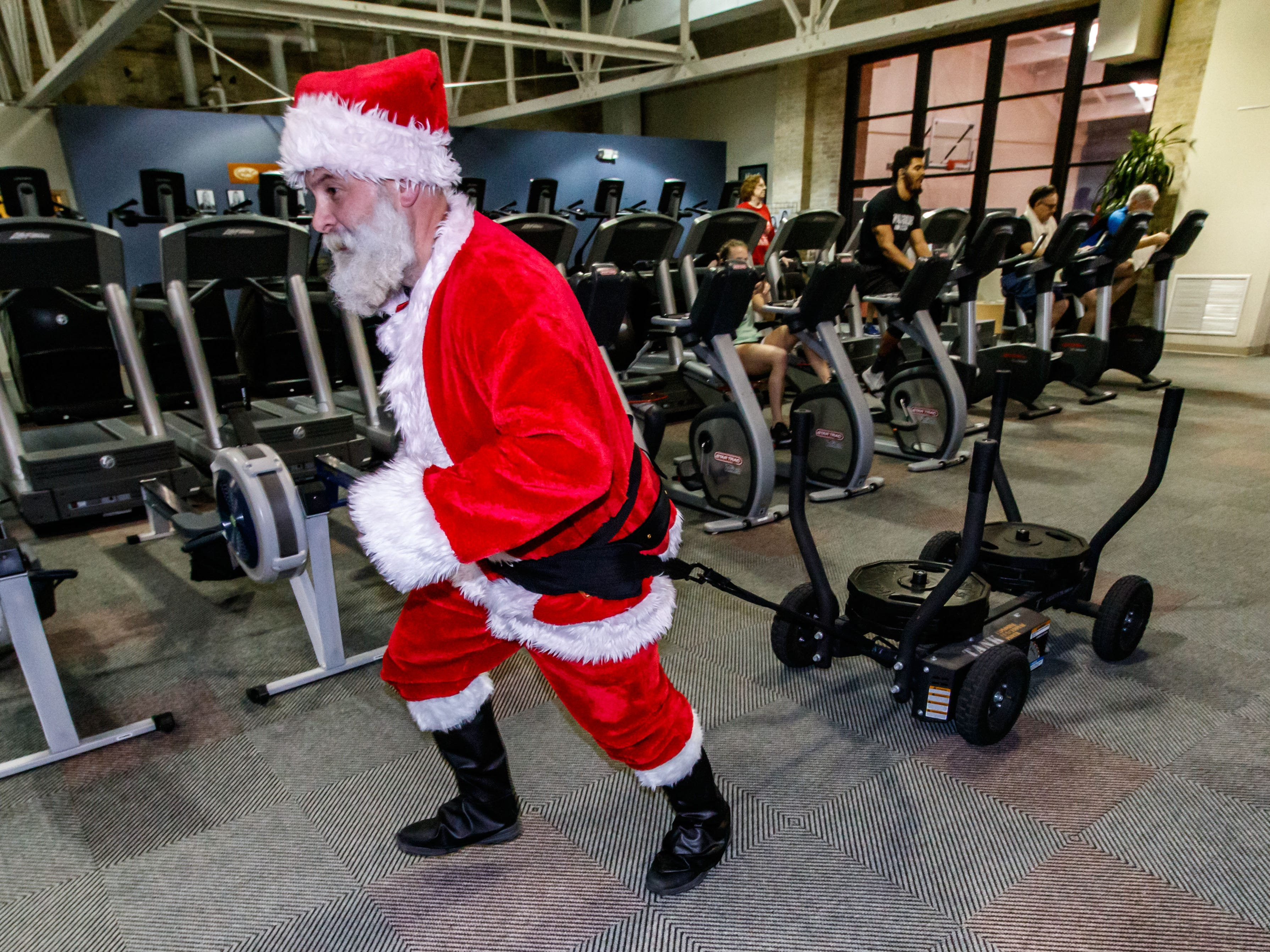 Derek Byrne tows a weight sled in full Santa attire at the Wisconsin Athletic Club in Wauwatosa on Monday, Dec. 10, 2018. Derek, who does strong man competitions and is involved in charity work, dresses up to encourage others to work out.