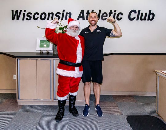Derek Byrne poses for a photo in full Santa attire with trainer Mark Baumhardt at the Wisconsin Athletic Club in Wauwatosa on Monday, Dec. 10. Derek, who does strong man competitions and is involved in charity work, dresses up to encourage others to work out.