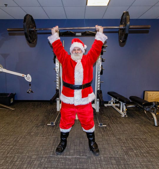 Derek Byrne performs an overhead press in his Santa attire at the Wisconsin Athletic Club in Wauwatosa on Monday, Dec. 10. Derek, who does strong man competitions and is involved in charity work, dresses up to encourage others to work out.