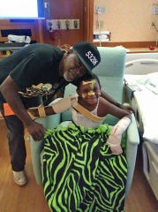 """Erik """"Doobie"""" Williams Jr. and Andre Lee Ellis take a picture in the hospital after the 4-year-old came out of a coma after he was was shot four times near North 10th and West Burleigh streets on Aug. 10."""