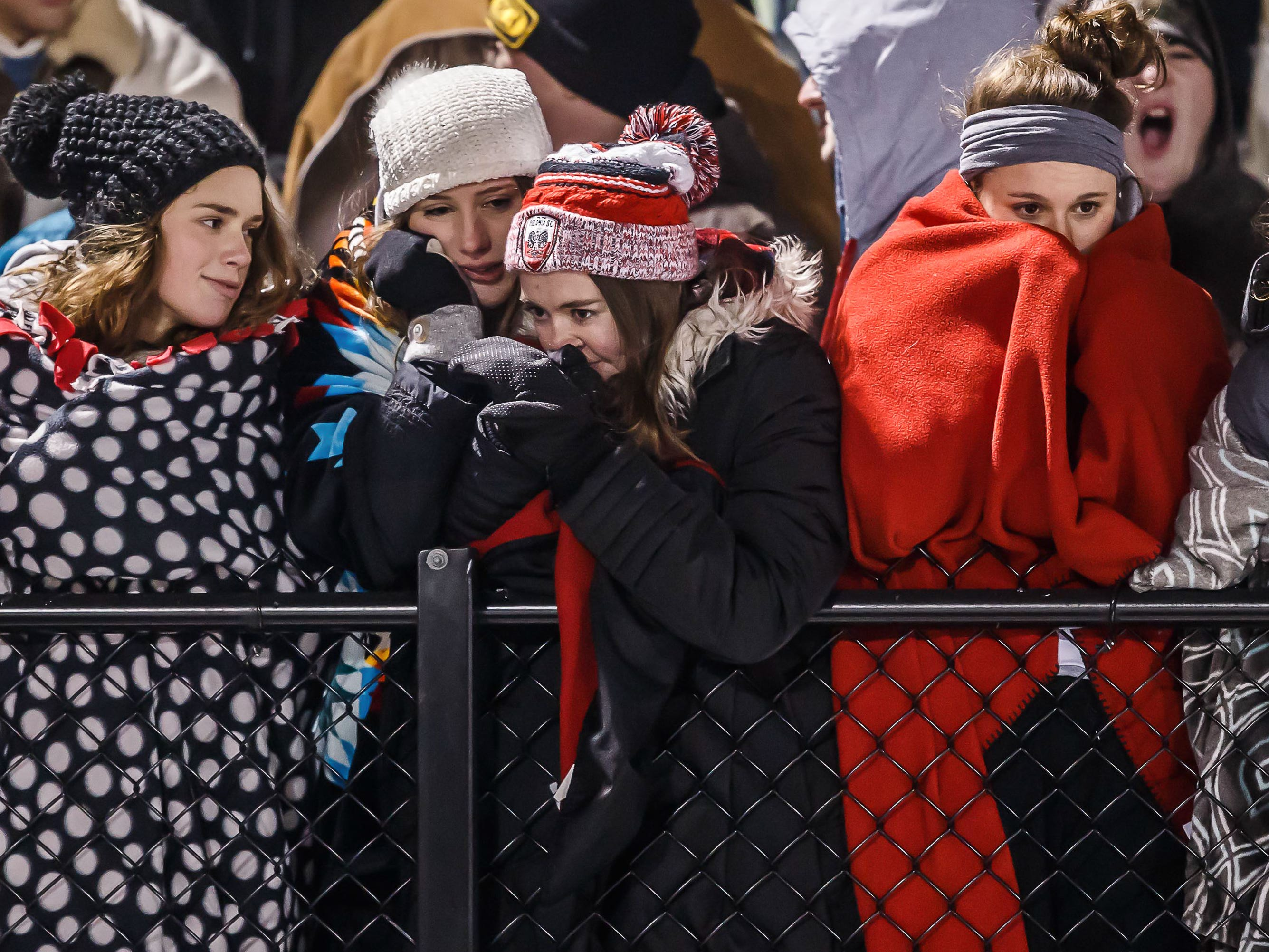 Muskego High School students brace against a single digit wind-chill during the WIAA Division 1 playoff game against Marquette University High School in Hartland.