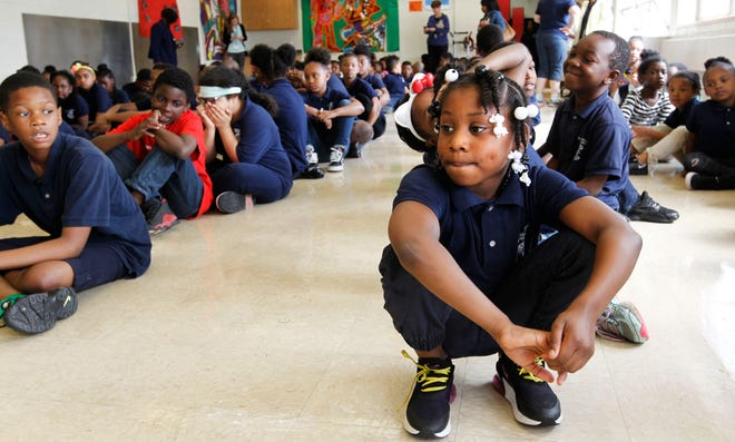 Sirryah Parks (right), a second grader at Carver Academy, sits with her class during the last student assembly of the school year. The assembly is a time for staff to recognize student success, reinforce school values and school spirit.