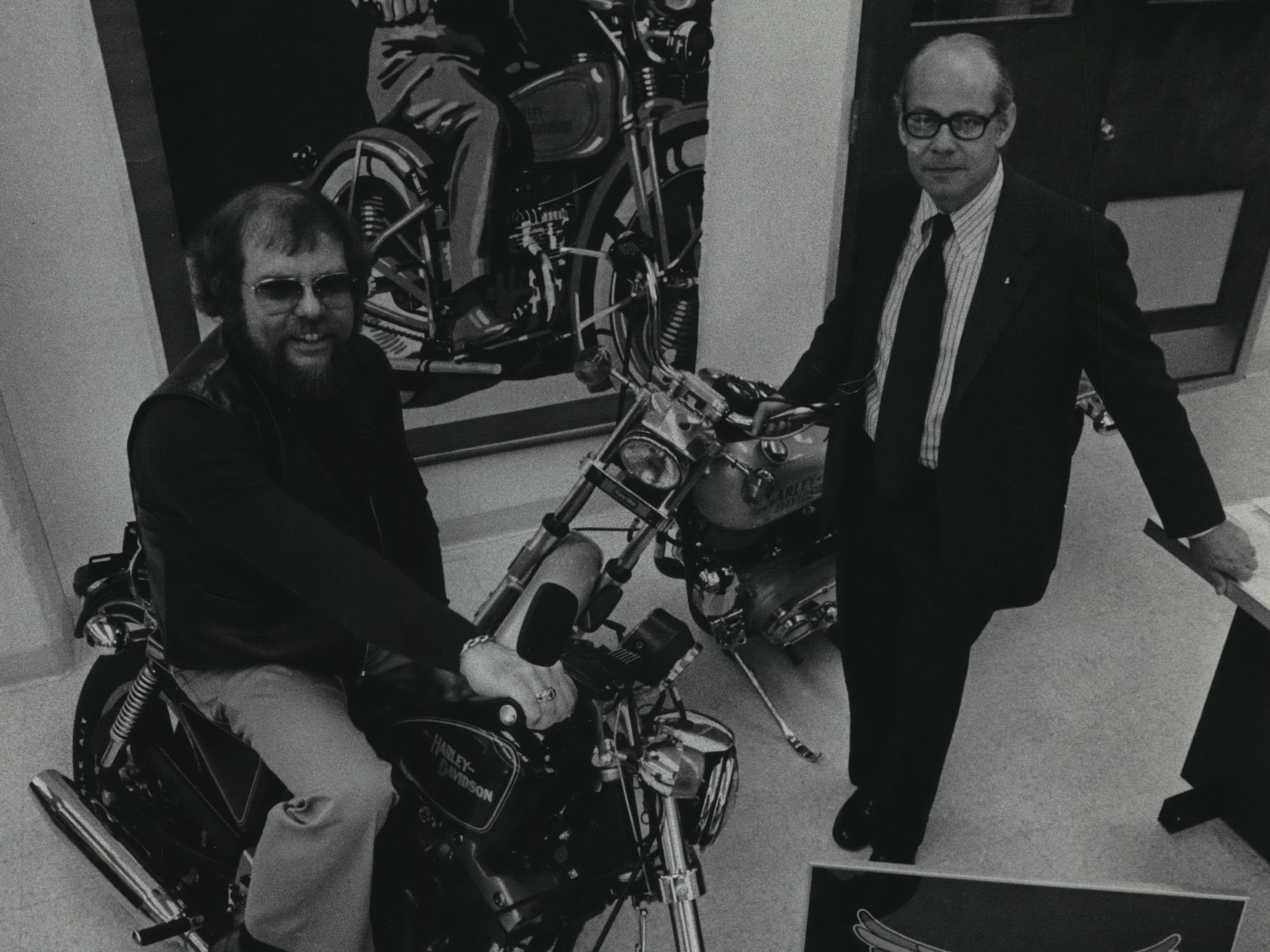 William (left) and John Davidson, the brothers who head the Harley-Davidson Motor Co., pose with some of the company's products in the lobby of Harley's Milwaukee headquarters during celebrations of the motorcycle manufacturer's 75th anniversary in 1978, a decade after Harley agreed to be acquired by AMF.