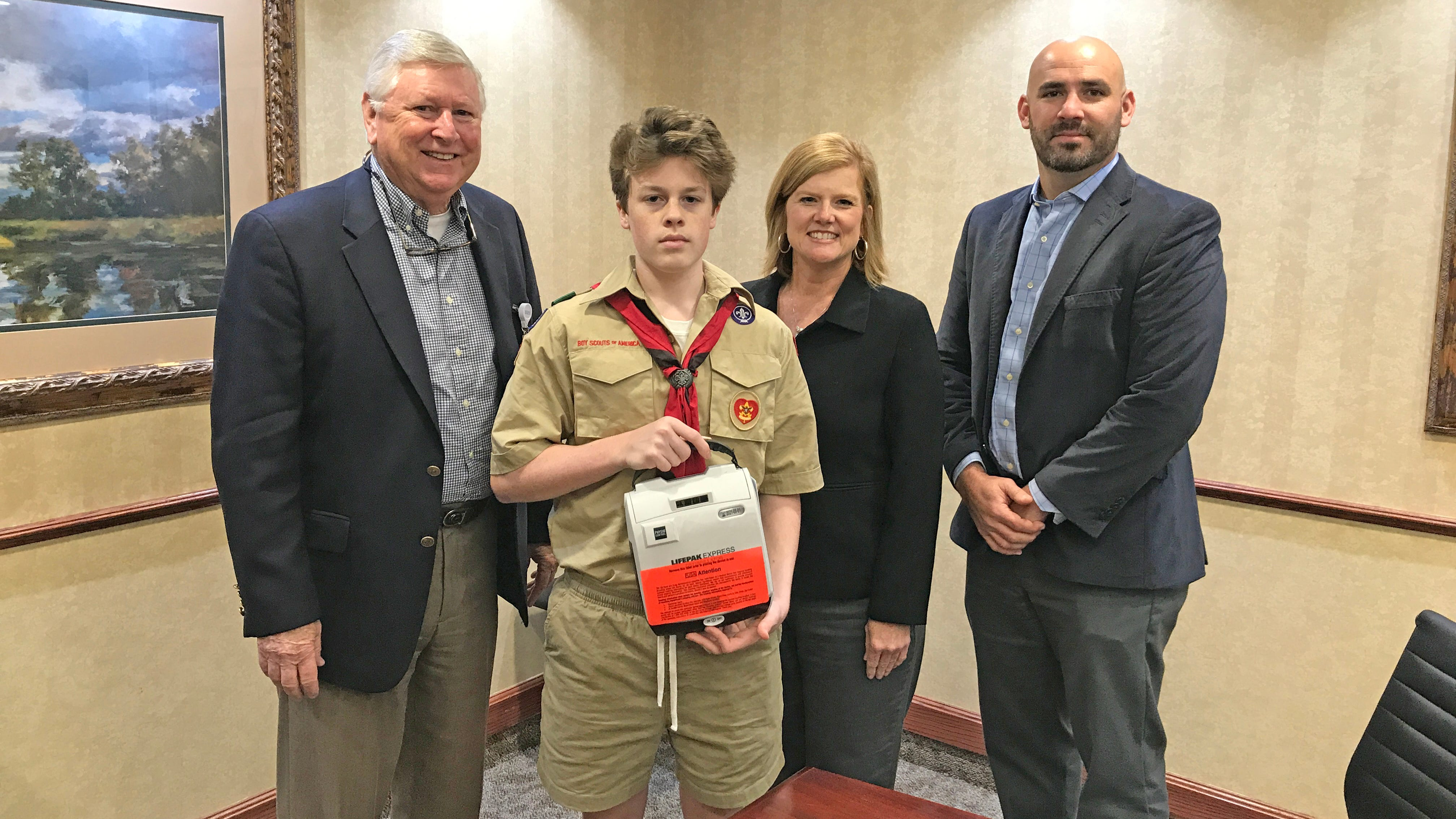 Ben Camp, a sophomore at MHHS and Eagle Scout candidate, displays one of the AEDs he helped secure for Mountain Home Public Schools. Also pictured are: (from left)Vice President of Business Development and the Executive Director of the Baxter Regional Hospital Foundation, Barney Larry; Dr. Leigh Anne Gigliotti, Mountain Home Public Schools Assistant Superintendent; and Dr. Jake Long, Mountain Home Public Schools Superintendent.