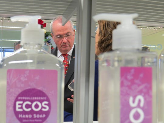 Gov. Phil Murphy examines eco-safe products manufactured by Earth Friendly Products in Parippany, where the company starts employees for a minimum of $17 per hour.