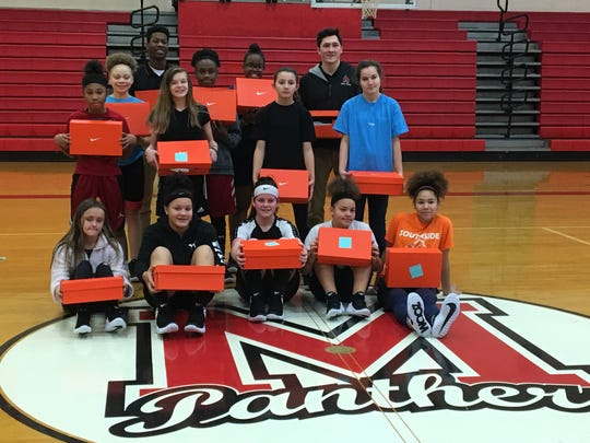 Players for Southside Middle School girls basketball teams stand with their new shoes at Monday night's practice. The shoes were donated thanks to $1,500 from Ball State's Interfraternity Council.