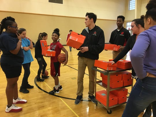 Coaches Jaleel Pryuer and Erik Hoglund pass out new shoes at Monday night's Southside Middle School girls basketball practice. The shoes were donated thanks to $1,500 from Ball State's Interfraternity Council.