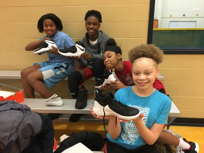 Players for Southside Middle School girls basketball teams pose with their new shoes at Monday night's practice. The shoes were donated thanks to $1,500 from Ball State's Interfraternity Council.
