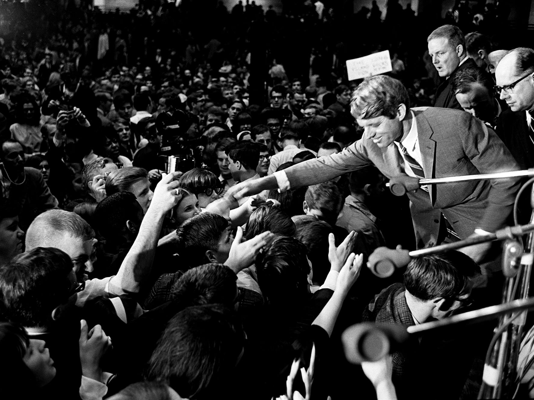 "Eager admirers strain to extend their hands and their support to presidential aspirant Sen. Robert Kennedy, right, after he delivered his address on the ""Destiny of Dissent"" to an overflow crowd of more than 10,500 during the Impact Symposium at Vanderbilt University on March 21, 1968."