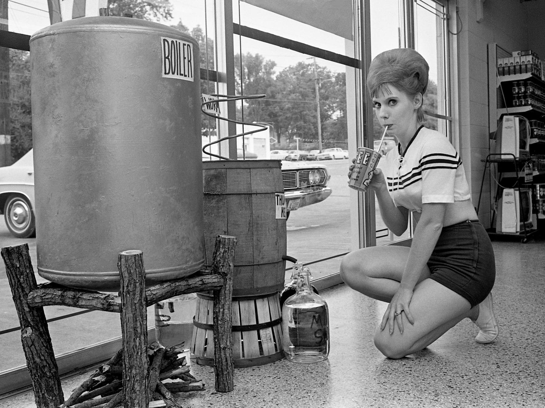 "Sherry Bullion, a customer of the Seven Eleven market at 1000 Gallatin Road, tries a new ""moonshine"" Icee on July 17, 1968, while inspecting what the manager, Frank A. Lynch, said is a ""real moonshine still,"" used in this case to dramatize the new Icee flavor."