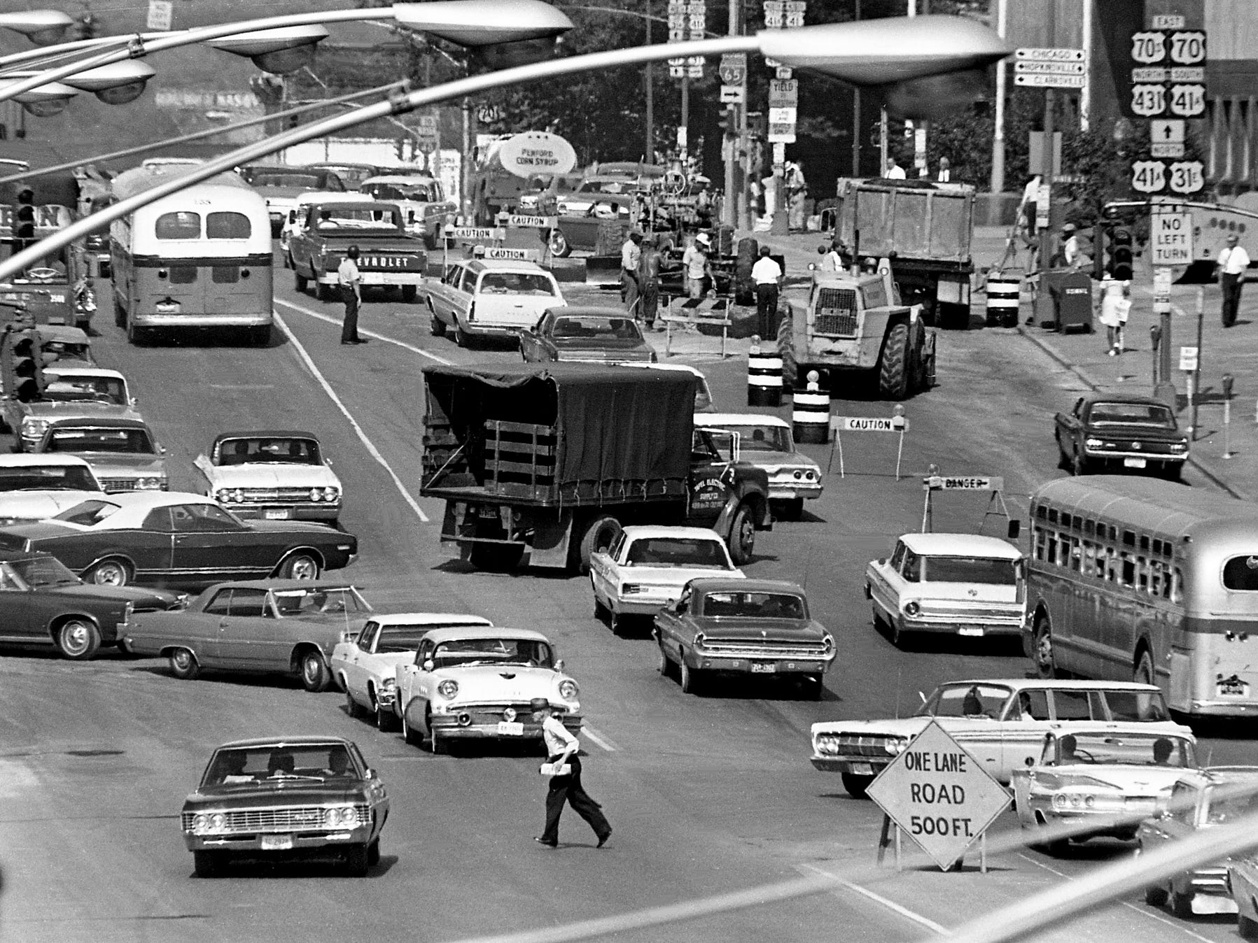 An elderly man weaves his way in and out of traffic snarled along Broadway between Eighth and Tenth Avenues, one of the busiest intersections in Tennessee, on Aug. 14, 1968. It is further cluttered and confused as workers attempt to resurface the street.