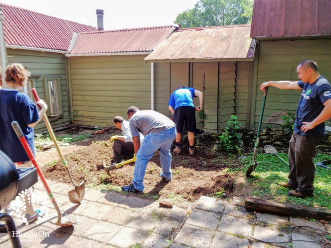 Volunteers work outside a home being repaired by Hands On Nashville.