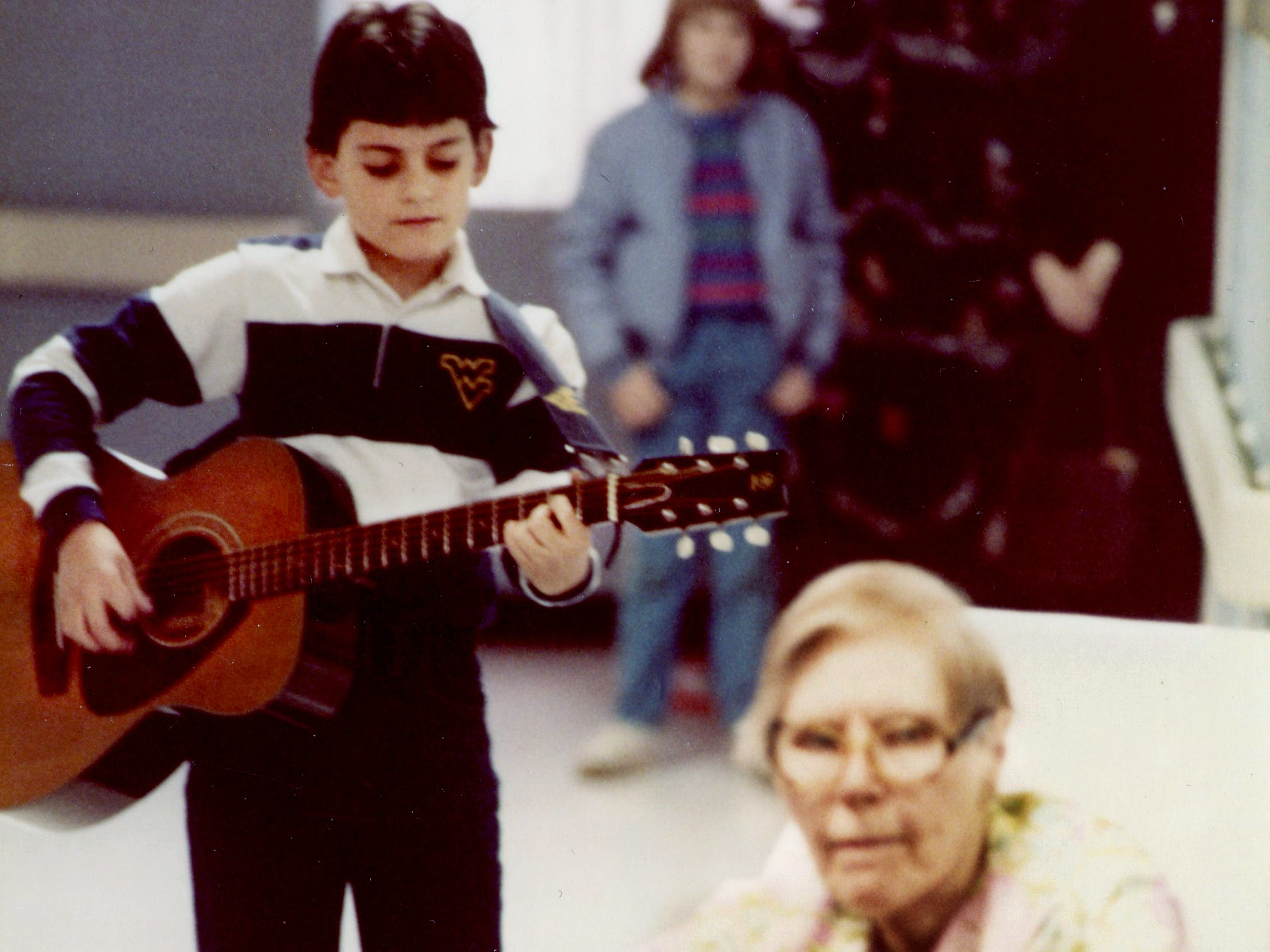 """Brad Paisley, 11, plays in a respite ward hallway at Reynolds Memorial Hospital in Glen Dale, W.Va. The patient in front of him was mostly nonverbal, yet she inexplicably sang along to every word when Paisley sang """"You Are My Sunshine"""" to her, an unlikely duet that had staff and Brad's mother, upper right, in tears."""