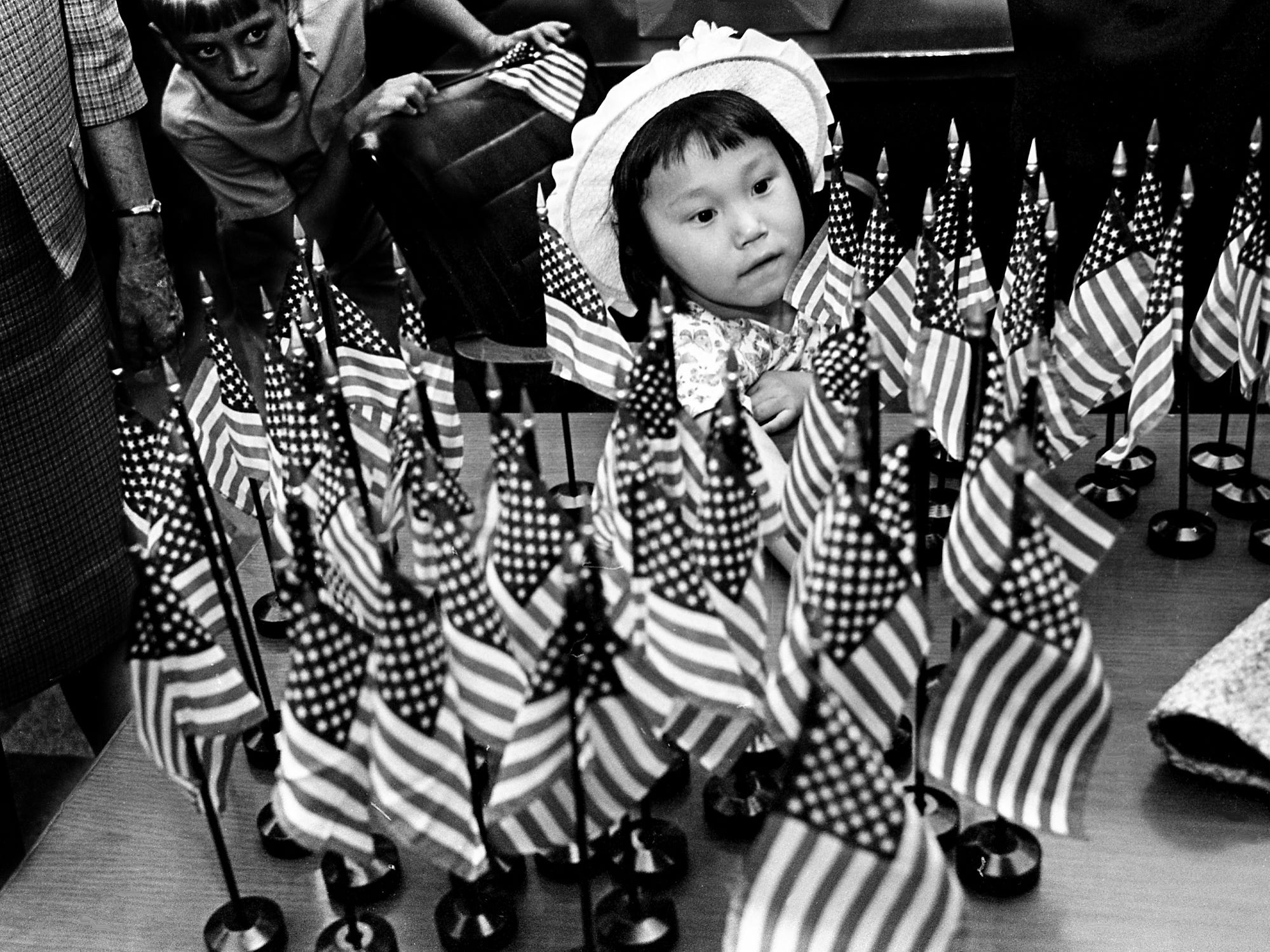 Deborah Herbert, once a Korean orphan, is surrounded by miniature flags of her newly adopted country after she was among the 60 members of the class of immigrants who became naturalized American citizens in Nashville on April 17, 1968. Deborah, 4½, is the adopted daughter of the Rev. Douglas G. Herbert, chaplain at Sewart Air Force Base, and his wife, Florence.