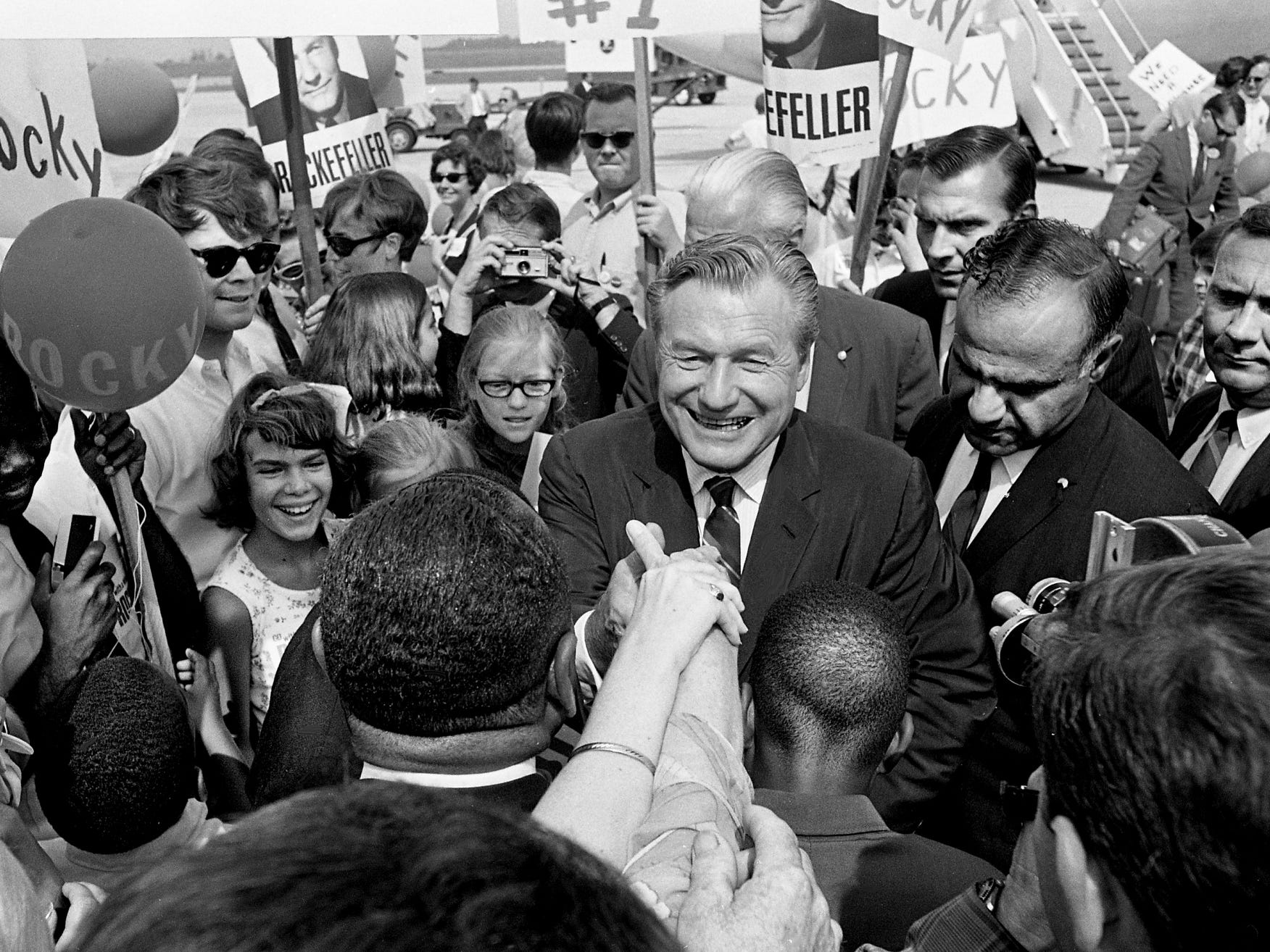 Gov. Nelson Rockefeller of New York shakes hands with enthusiastic supporters who met the Republican presidential nominee upon his arrival at Nashville Municipal Airport on July 9, 1968.