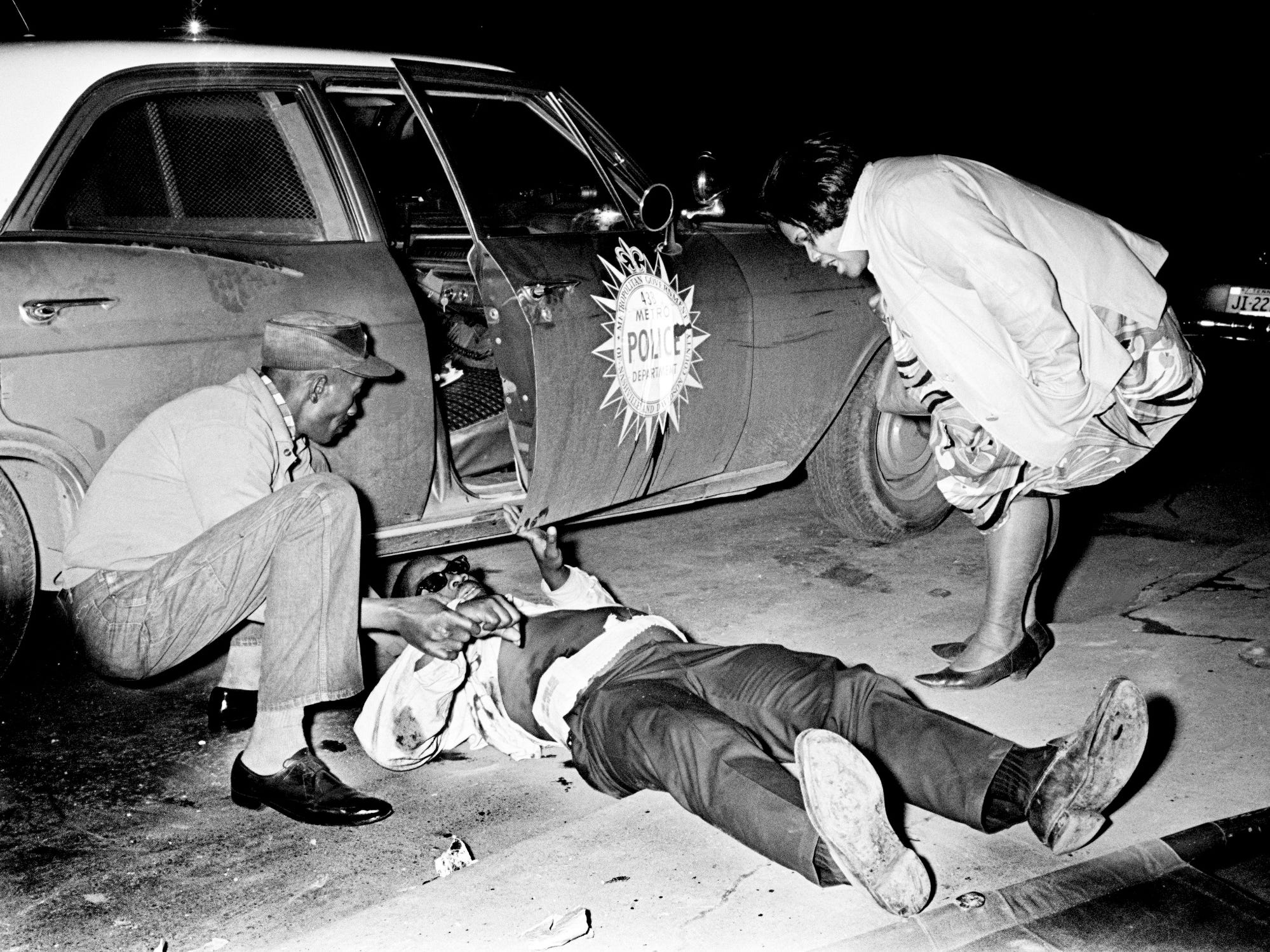A couple of friends check on Elvis Fleming, center, 50, of Pecan Street, after he was wounded during a Metro police gunbattle April 4, 1968. Fleming and 13-year-old Anthony Webster were hurt when police were summoned to 22nd Avenue and Osage Street to check on a complaint that an armed person was threatening residents during rioting after the assassination of the Rev. Martin Luther King Jr.