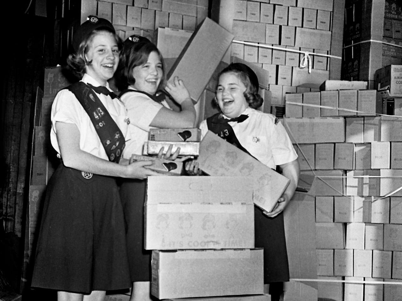 Girl Scouts Trudie Hostettler, left, Carol Nance and Heidi Damberg get a look at some of the 600,000 boxes of cookies at the warehouse Feb. 16, 1968, that will be sold during the 10th annual Girl Scout Cookie sale.