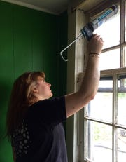 Hands On Nashville volunteer Meghan Scholl seals a window frame of a house under repair.