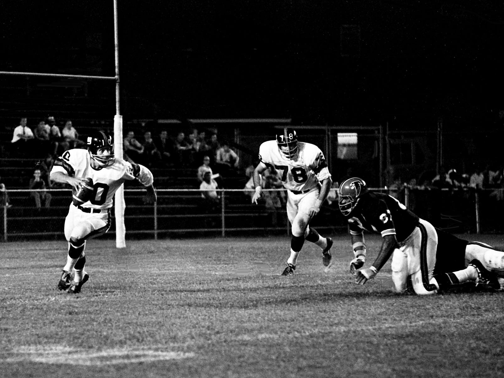 Atlanta Falcons rookie Claude Humphrey (87), right, can only look on as New York Giants quarterback Fran Tarkenton (10) starts to head up the field as the two teams battled at Vanderbilt's Dudley Field during a preseason matchup Aug. 17, 1968. The Giants came out on top 17-13 before a disappointing size crowd of 14,455.