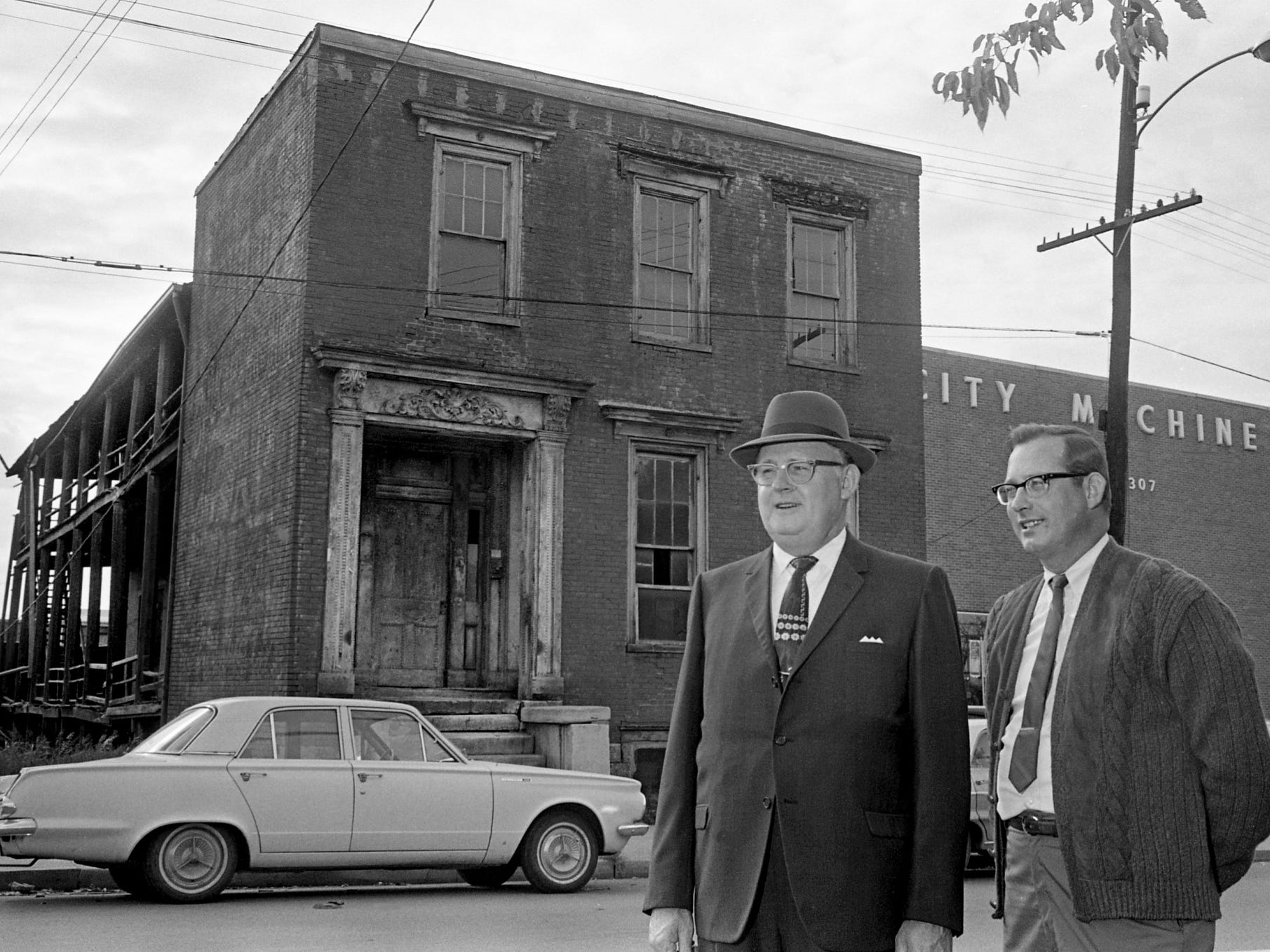 Ward Lovell Sr., left, and Ward Lovell Jr., president and vice president of Rock City Machinery Co., stand outside the house adjacent to their business Oct. 22, 1968, that they purchased for expansion. The house has not been occupied for several years and is said to have been used as a hospital during the Civil War. The building will be razed for the firm's expansion plans.