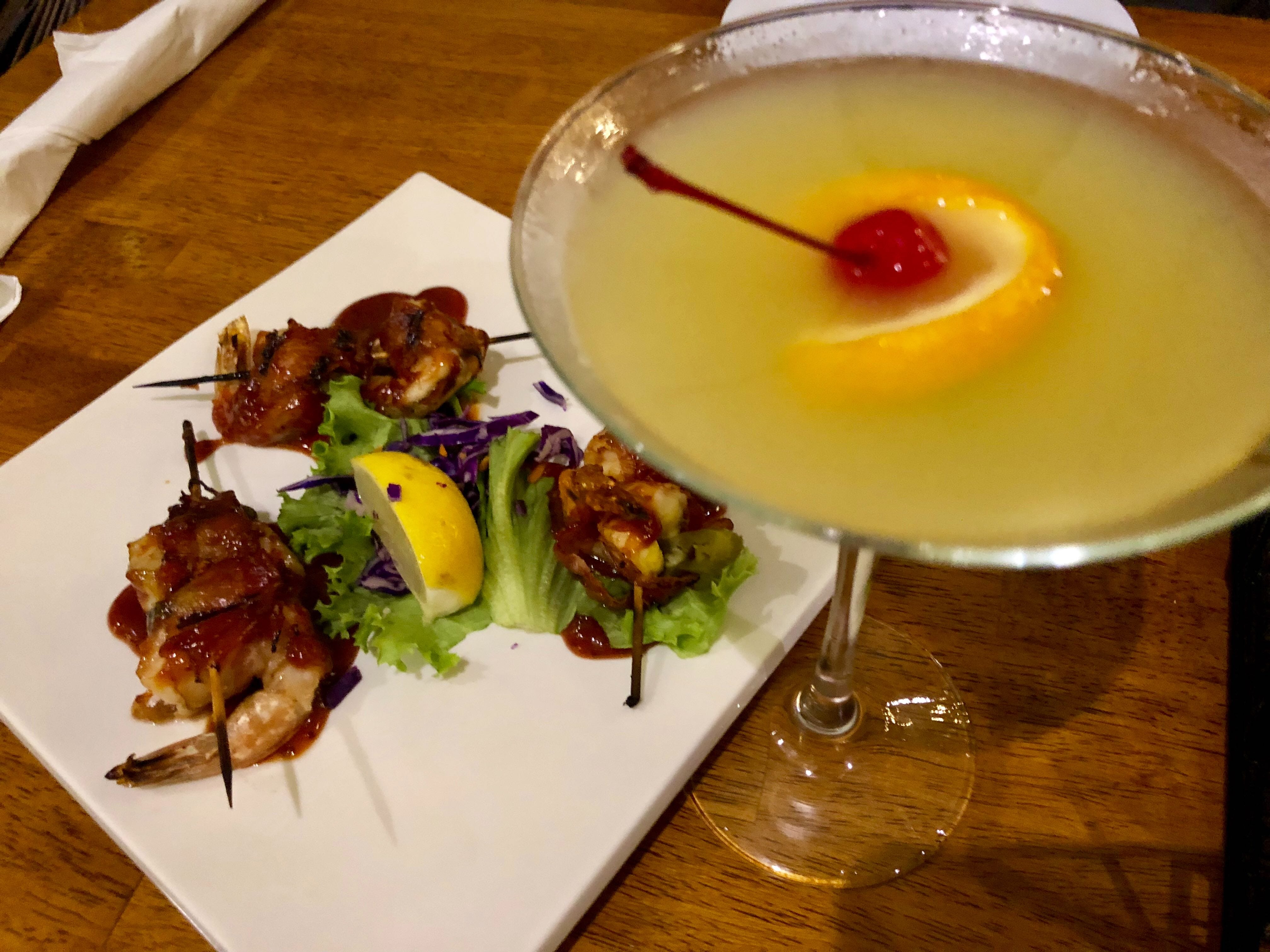 Shrimp stuffed with jalapeno slivers, wrapped in bacon and glazed in barbecue sauce at  Alice Sweetwater's Bar & Grille. A white wine sangria martini is the restaurant's signature drink.