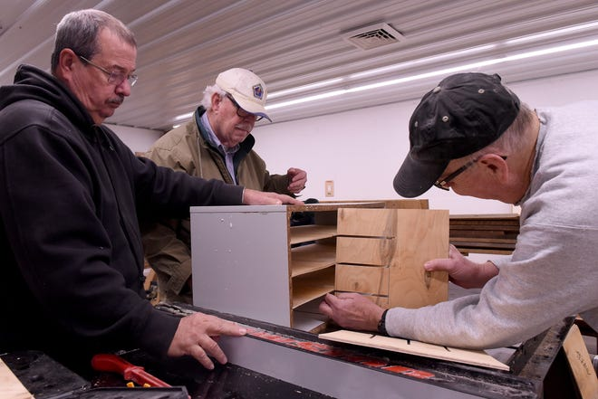 Dan Johnson, David Chenault, and Jim Thompson build shelving for sandpaper storage while working to set up the new woodworking shop for Craftsmen for Kids in Hebron.