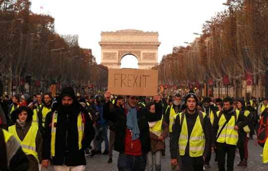 Demonstrators known as the yellow vests march down Paris' famed Champs-Elysees Avenue, France, Saturday, Dec. 8, 2018. Prized Paris monuments and normally bustling shopping meccas locked down Saturday and tens of thousands of police took position around the country, fearing worsening violence in a new round of anti-government protests. (AP Photo/Michel Euler)