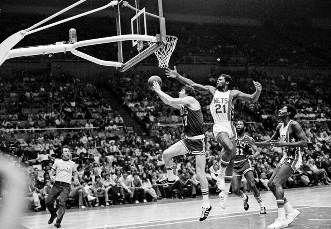 Boston Celtics John Havlicek on the way to a basket as New York Nets tim Bassett tries to block the score in their game at Uniondale, N.Y., Dec. 20, 1976. Celtics Tom Boswell is the looker. Celtics won, 94-87. (AP Photo/Harry Harris)