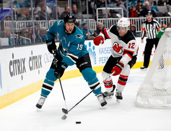 San Jose Sharks' Joe Thornton (19) battles for the puck against New Jersey Devils' Ben Lovejoy (12) in the first period of an NHL hockey game in San Jose, Calif., Monday, Dec. 10, 2018. (AP Photo/Josie Lepe)