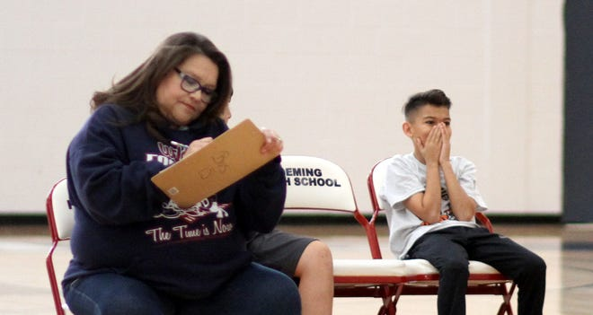 Nathan Quiroz is overcome with emotion upon learning he is the winner of the Deming Elks Hoop Shoot for the boys' age 12013 division. Keeping score is Deming Elks member Dolores Teague.