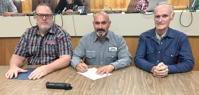 Deming Mayor Benny Jasso, center, signs into proclamation the Luna County Shop with a Cop Certificate of Appreciation in memory of Jenny Cowles, founder of the annual charitable event. At left is jenny's son, Curt Cowles and her husband Len Cowles, at right.