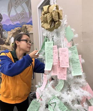 Peppers Supermarket employee Lulu Morales looks over the Tree of Hope to find a tag she can shop for before Christmas Eve.