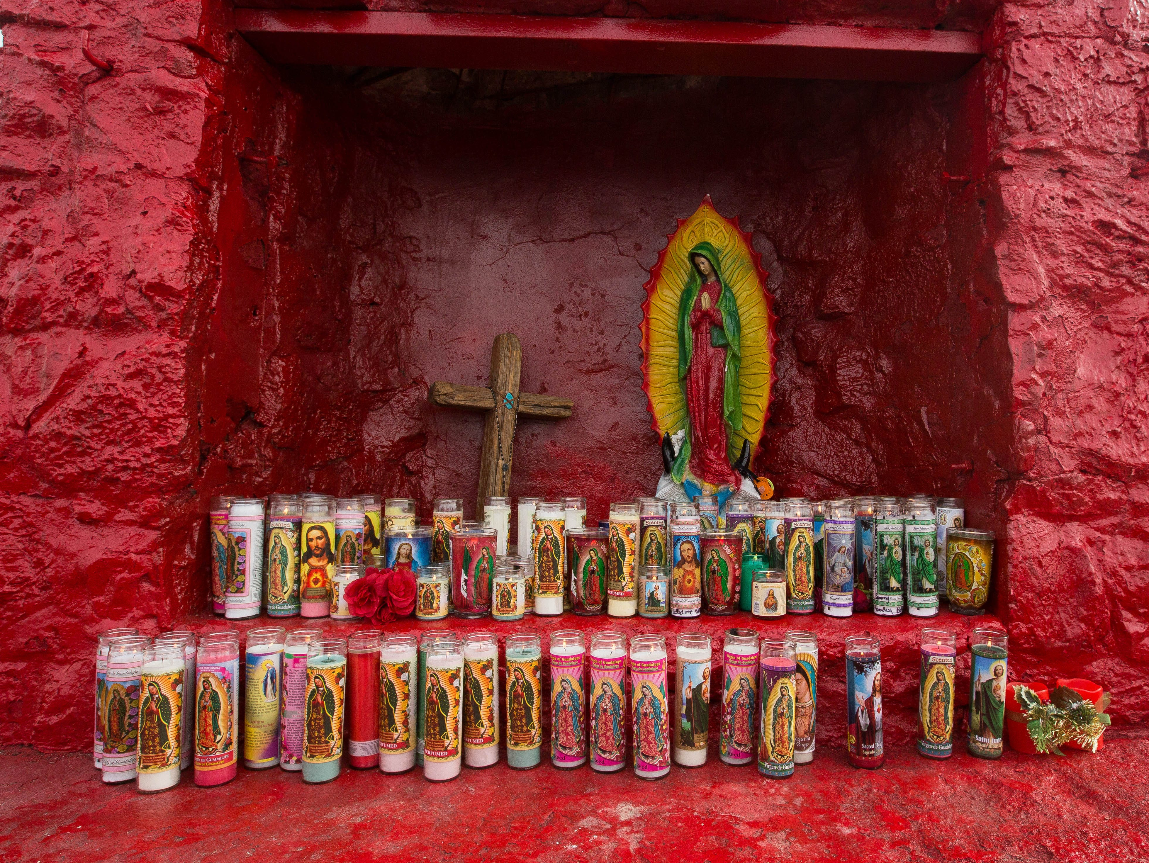 The altar to the Virgen de Guadalupe on top of Tortugas Mountain is adorned with candles placed by pilgrims during the second day of the Fiesta of Our Lady of Guadalupe on Tuesday, Dec. 11, 2018.
