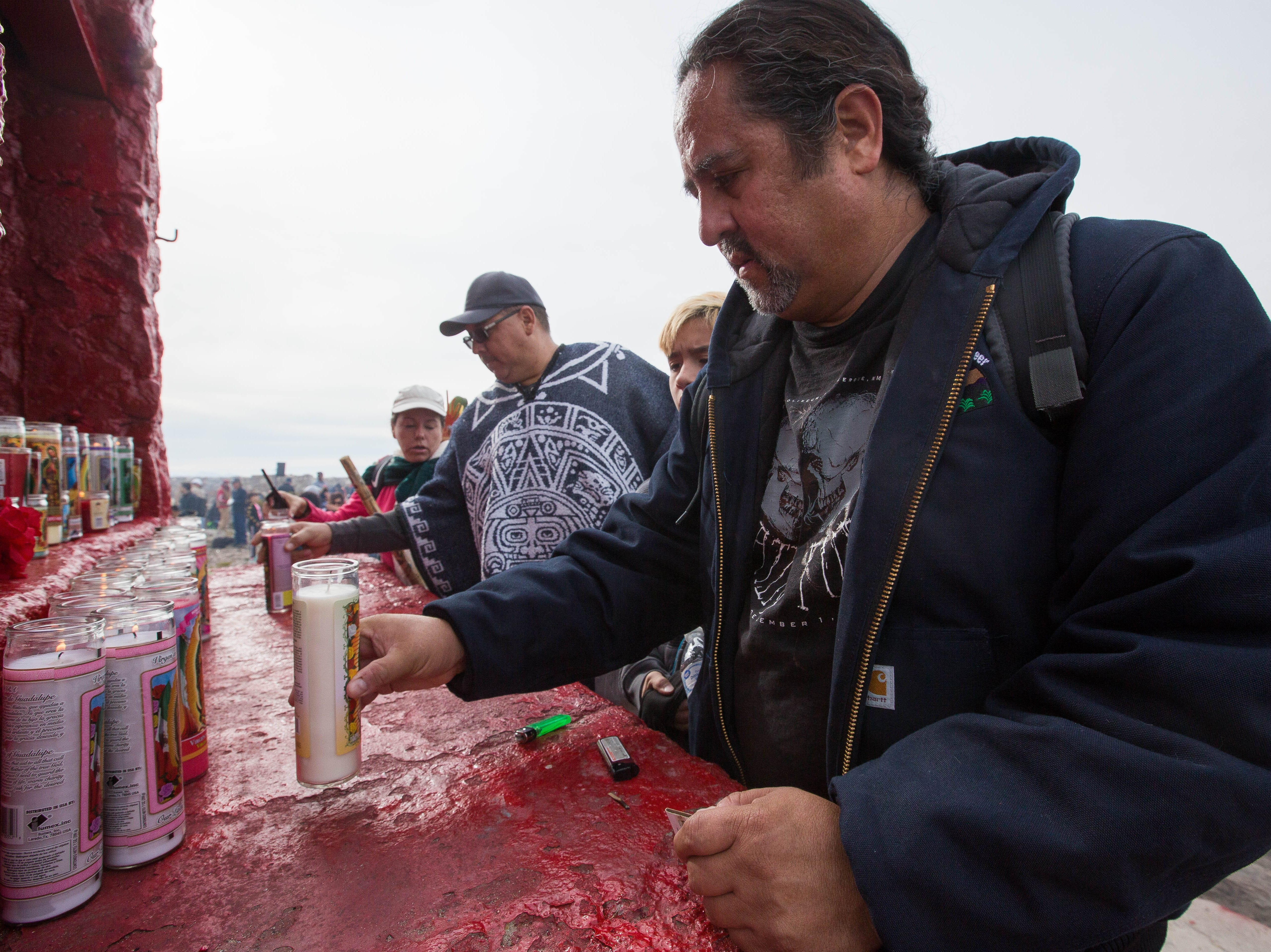 Juan Carlos Benavides, right, and his son Alejandro Rafael Benavides, 10, left, place a lit candle on the alter at the top to the Tortugas Mountain on Tuesday Dec. 11, 2018. Benavides hiked up the mountain during the pilgrimage to pray for their family during the second day of the Fiesta of Our Lady of Guadalupe.