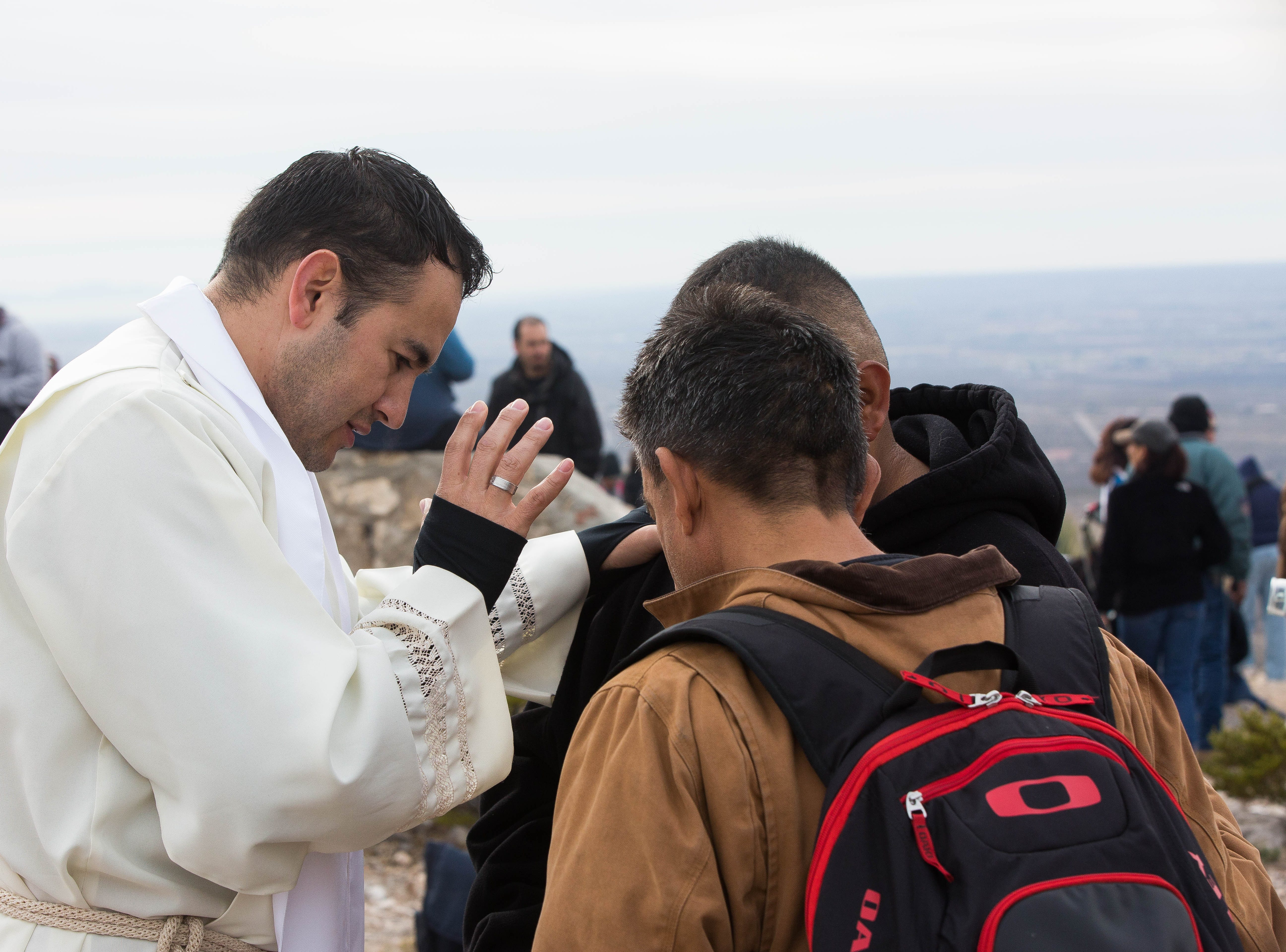 Father Alex Urena, from St. Albert the Great Newman Center, gives a blessing to father and son Eddie Ortiz Sr. and Eddie Ortiz Jr., on Tuesday Dec. 11, 2018, on top of Tortugas Mountain.