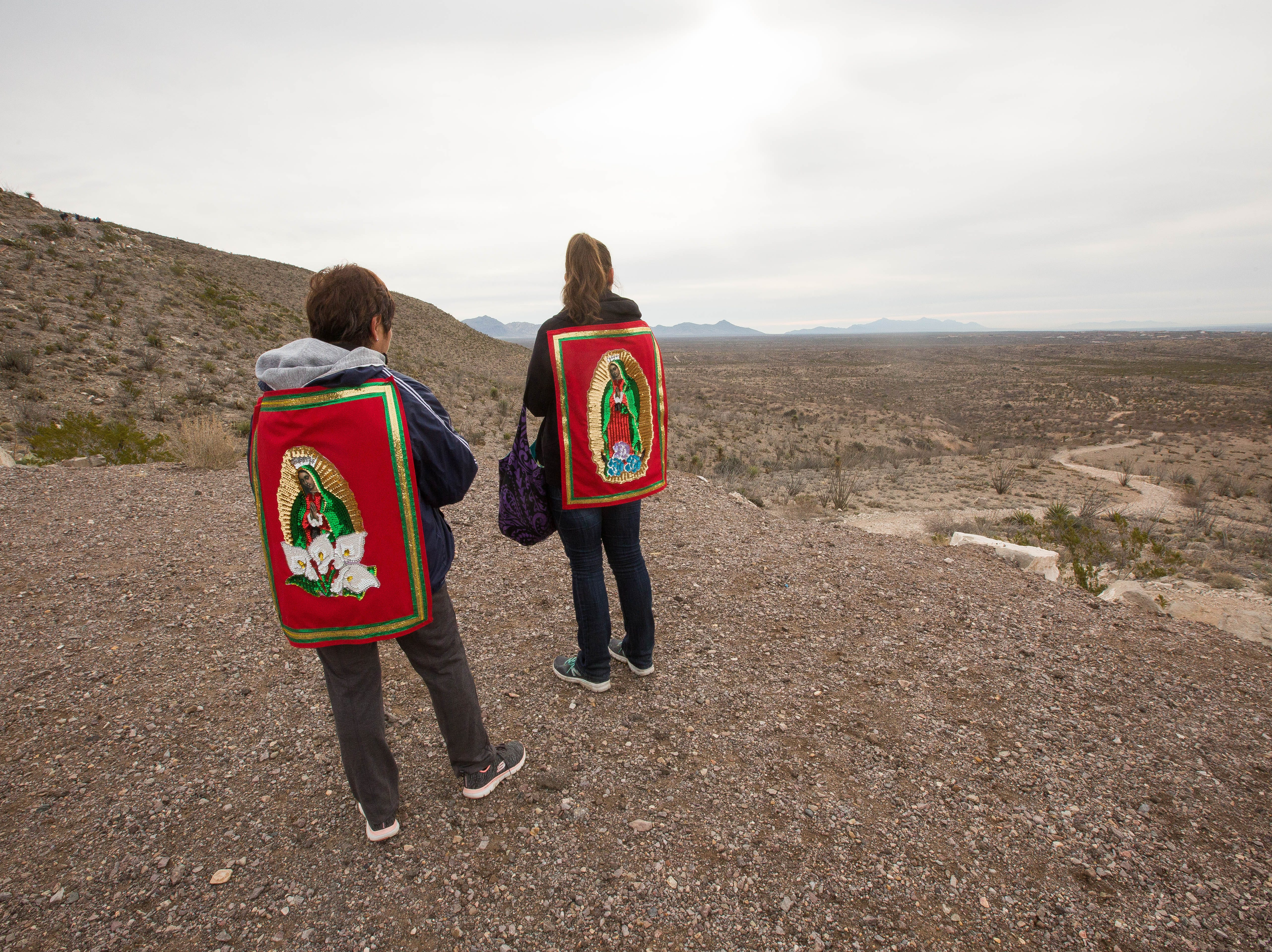 Giovanna Musitano, left and her mother Ramona Musitano, right, take a break as they hike up Tortugas Mountain as part of a pilgrimage from the Tortugas Pueblo to the top of the mountain, Tuesday Dec. 11, 2018.