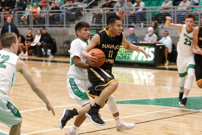 Navajo Prep's Thomas Montanez lunges forward attacking the basket against Farmington during Saturday's Marv Sanders Invitational championship game at Scorpion Arena in Farmington. The Eagles are now the sixth-ranked team in the latest 3A poll.