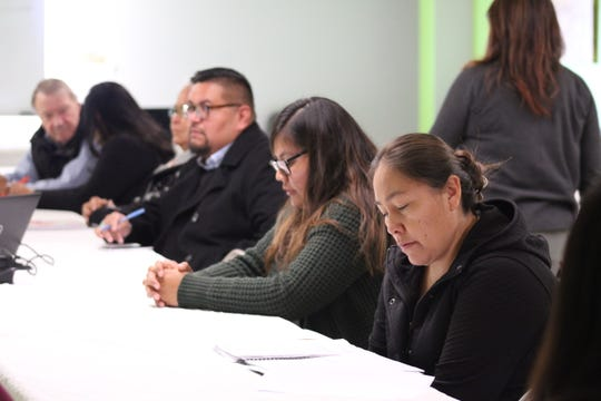 At right, Junette Russell, an employee for the Bureau of Indian Education school in Lukachukai, Ariz., reviews her notes before a presentation at the Navajo Pride Benefit Fund luncheon on Dec. 4 at the Navajo Agricultural Products Industry headquarters.