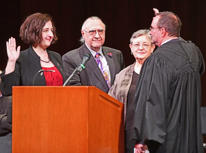 District Judge Krista Haroutunian (left)  is sworn in by retired Third Circuit Court Chief Judge Robert J. Colombo (right) as her parents, Edward Haroutunian and Susan Licata Haroutunian look on.
