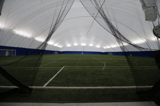 A seasonal dome covers an outdoor synthetic turf field in winter.