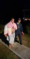 Midway Fire District firefighter/EMT Cale Secondine wraps himself in blankets just minutes after diving into cold water to rescue a citizen's dog. Daisy, the dog, had gotten stuck in between two boards underneath a dock. She was cold, but unharmed.