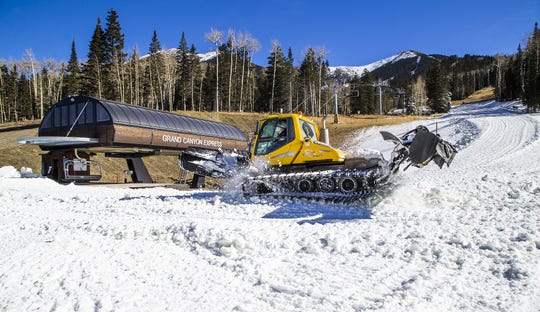 Machine-made snow is spread around near the Grand Canyon Express chairlift, Thursday, November 15, 2018, at Arizona Snowbowl.