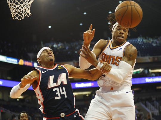 LA Clippers forward Tobias Harris (34) and Phoenix Suns forward Richaun Holmes (21) fight for a rebound during the first half in Phoenix, Ariz. December 10.
