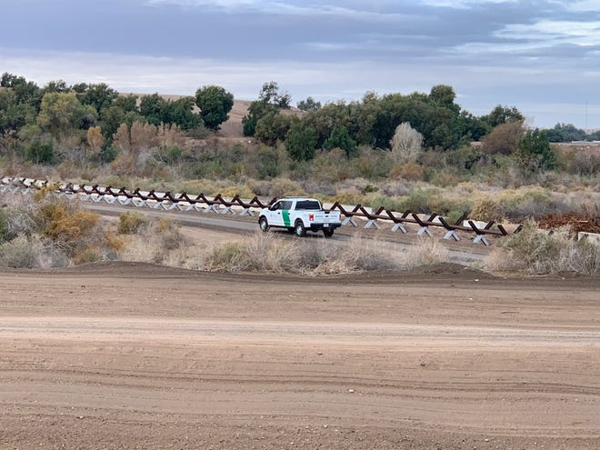 A Border Patrol vehicle drives past Normandy barriers built along the wooded areas of the Colorado River, with Mexico in the background. An increasing number of families are opting to cross the border illegally through here.