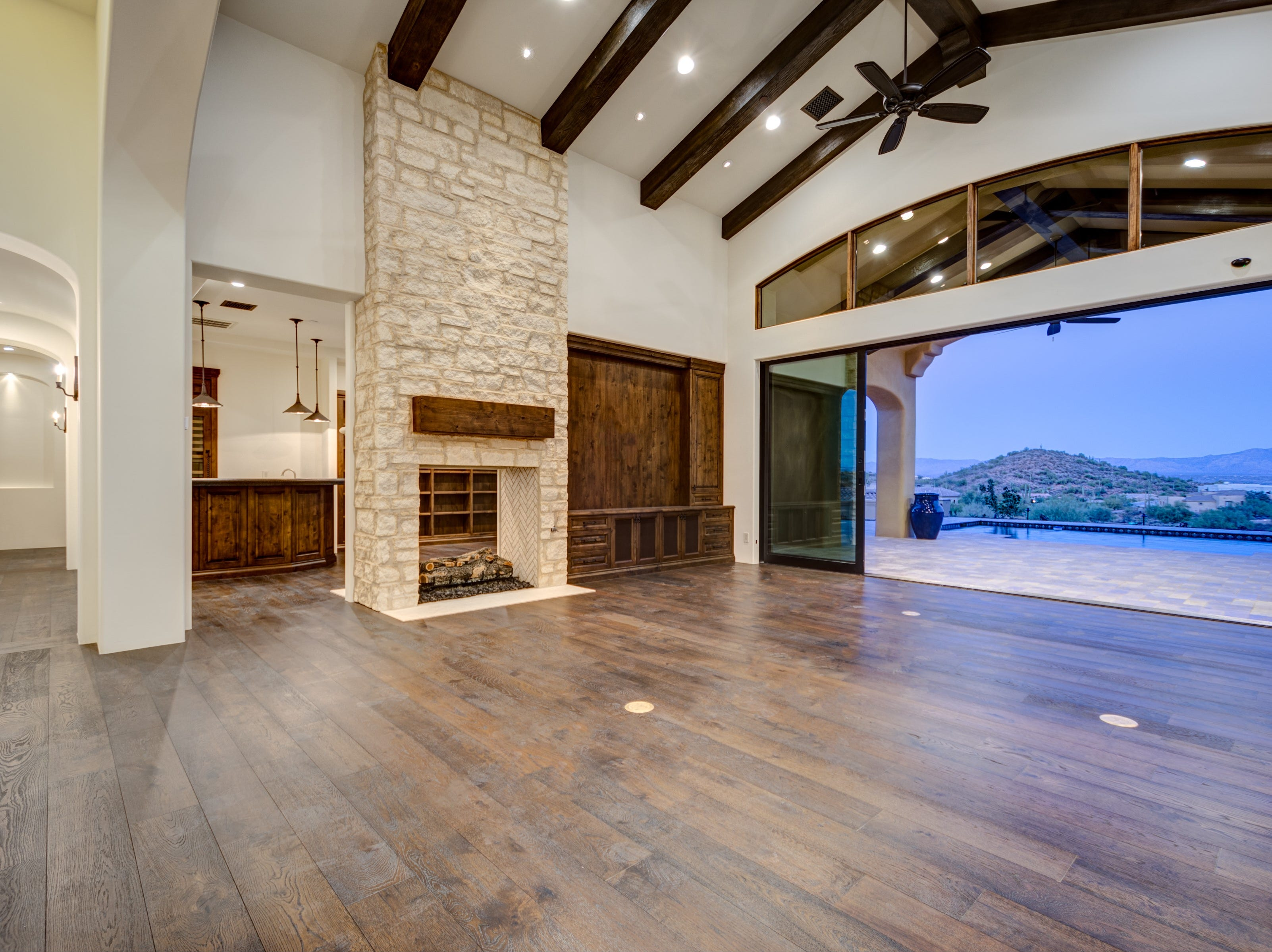 This Fountain Hills home features vaulted beamed ceilings and glass wall doors that open to a backyard that has mountain views.