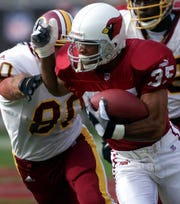 Cardinals cornerback Aeneas Williams eludes Redskins tight end Stephen Alexander after recovering a fumble during a 2000 game at Sun Devil Stadium.