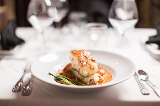 Sea Bass Ixchel, a traditional Mayan dish of fresh Chilean sea bass filet served on a bed of vegetables in a garlic-chipotle chile sauce.